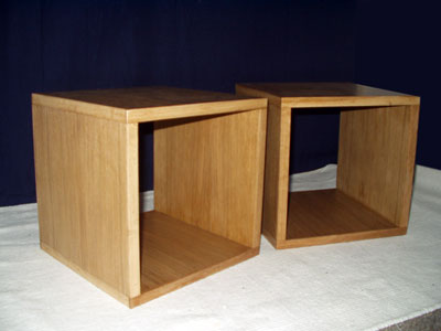 Side view of a pair of bedside tables in the form of a cube with open back and front
