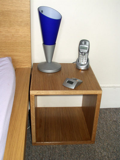 One of a pair of bedside tables next to a matching bed. A contemporary style blue lamp is placed on the table