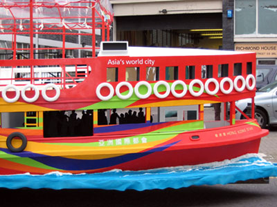 Side view of a red boat with yellow, green and blue wavy stripes on the hull and a large glassed-in promenade deck