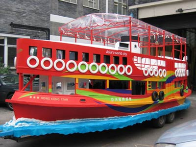 Three-quarter view of a parade float in the form of a large red boat on carved waves, mounted on a trailor
