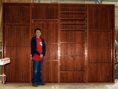 Front view of a set of tall free-standing bookshelves with me standing in front of them for scale
