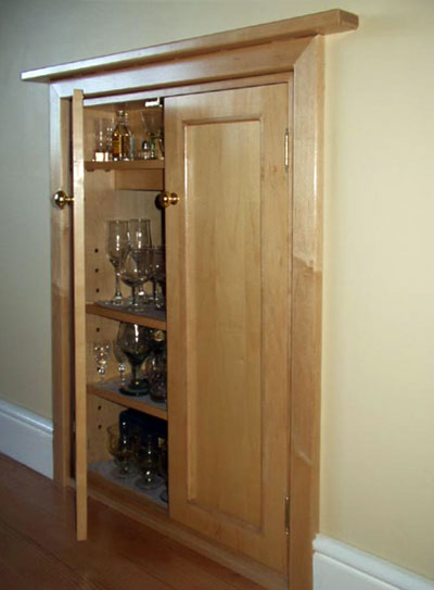 Three-quarter view of a built-in drinks cabinet with three shelves, one door open and one closed