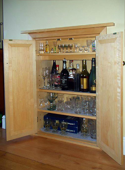 Three-quarter view of a built-in drinks cabinet with three shelves, the doors open to show the interior with bottles and glasses