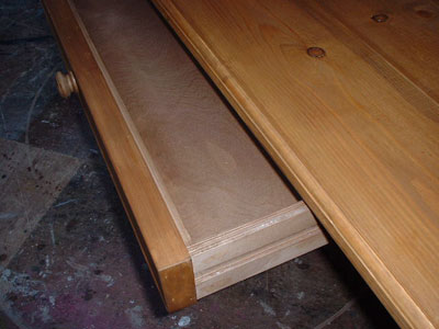 Close up of the open drawer of a large pine table, showing the interior