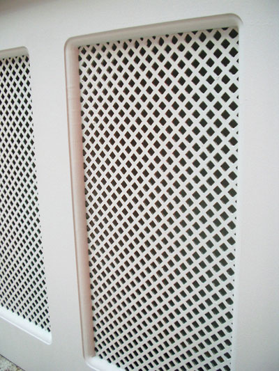 Close-up of the inset mesh panel of a wooden radiator cover, finished in gloss white