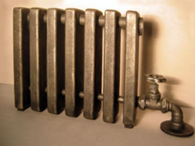 Front view of a old-fashioned radiator with a wheel-valve on the right side