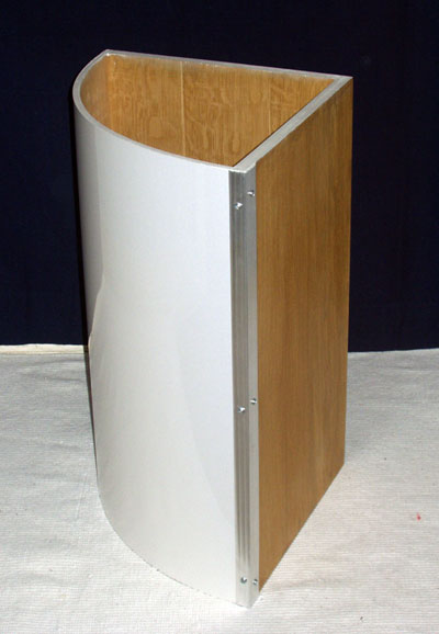 Side view of a curved white washing basket showing aluminium trim and oak-veneered sides
