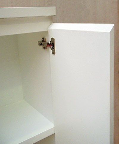 Close up of the top right corner of a white cabinet, the door open to show the silver door fixings