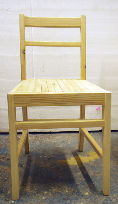 Front view of a pale coloured simple wooden chair