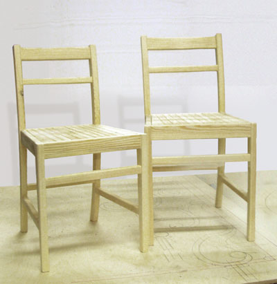 A matching pair of pale coloured wooden chairs